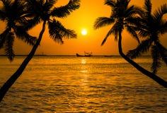 Silhoutte-Kokosnuss-Palmen mit silhoutte Fischerboot auf tropischem Meer im Sonnenuntergang Lizenzfreie Stockbilder