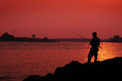 Silhoutte of a man fishing Royalty Free Stock Images