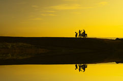 Silhoutte of a man standing with his bike during beautiful golde Stock Images