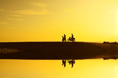 Silhoutte of a man standing with his bike during beautiful golden sunrise. Stock Photos