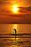 Silhoutte of a fisherman holding a nett to catch a fish Royalty Free Stock Photos