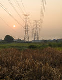 Silhoutte power lines and pylons at sunset. Stock Photo