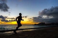 Silhoutte van agentjogging langs Waikiki-strand Stock Afbeeldingen
