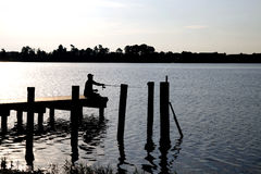 Silhoutte van visser op dok stock foto