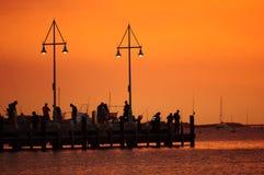 Silhoutte van vissers bij zonsondergang Stock Foto
