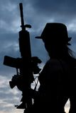 Silhoutte of  woman with gun. A silhouette of a stylish young woman wearing black and holding an assault rifle Royalty Free Stock Photo