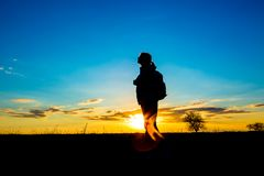 Silhoutte of woman hiker over sunset sky royalty free stock photos