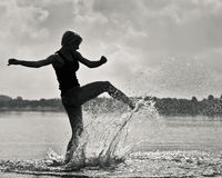 Silhoutte of woman playing in water Stock Images