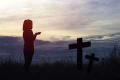 Silhoutte of women prayer and cross in evening and twilight. Halloween background Stock Images