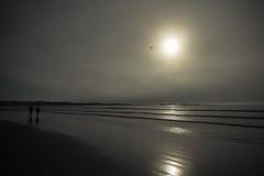 Silhoutted par som går på den dimmiga stranden royaltyfri bild