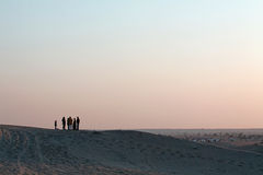 Silhoutted  People Group and Child on Sand-dunes at Dusk. Silhoutte of Group of People with Small Child in Discussion standing on Sand-dunes with Large Expanse Stock Photo