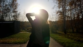 Silhoutter av en stilfull kvinna för yound som går av en kamera på, parkerar framme på solnedgången Beundra naturen i sommar stock video