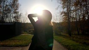 Silhoutter di una donna alla moda del yound che cammina davanti ad una macchina fotografica al parco al tramonto Ammirare natura  archivi video