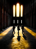 Silhouttes of three people walking through sunlight in an convent. Three persons walking into sun beams streaming through the windows of an old convent Stock Images