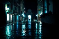 Silhouttes walking through arch on wet cobbled streets in Zadar, Croatia stock photo