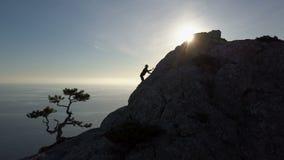 Silhueta aérea da jovem mulher que escala até a parte superior de uma montanha na frente do mar Voo sobre a senhora no filme