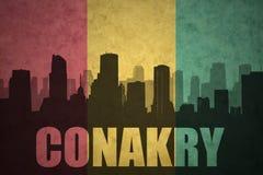 Silhueta abstrata da cidade com texto Conakry na bandeira da Guiné do vintage fotos de stock