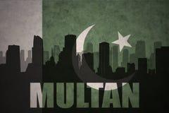 Silhueta abstrata da cidade com texto Multan na bandeira de Paquistão do vintage Imagem de Stock Royalty Free