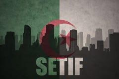 Silhueta abstrata da cidade com texto Setif na bandeira do argelino do vintage Imagens de Stock Royalty Free