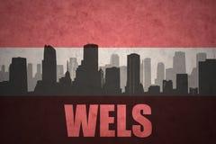 Silhueta abstrata da cidade com texto Wels na bandeira do austríaco do vintage fotos de stock