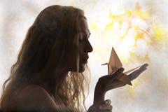 A silhueta bonita da mulher e origâmi crane em sua palma Fotografia de Stock Royalty Free