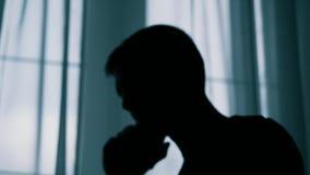 A silhueta borrada anônima de um homem que fala em um telefone celular, um criminoso está arrancando o dinheiro video estoque