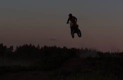 Silhueta borrada do cavaleiro do motocross que salta na montanha no por do sol Imagens de Stock Royalty Free