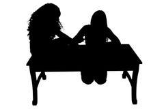 Silhueta com as meninas do trajeto de grampeamento na tabela Imagens de Stock