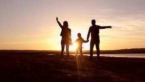 Silhueta, criança feliz com mãe e pai, família no por do sol, verão Corra, aumentando o bebê acima no ar, abraços, amor, jogando video estoque