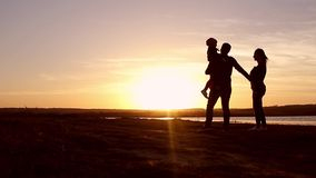 Silhueta, criança feliz com mãe e pai, família no por do sol, verão Corra, aumentando o bebê acima no ar, abraços, amor, jogando vídeos de arquivo