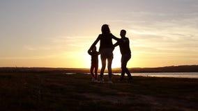 Silhueta, criança feliz com mãe e pai, família no por do sol, verão Corra, aumentando o bebê acima no ar, abraços, amor, jogando filme
