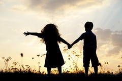 Silhueta, crianças felizes que jogam no prado Fotografia de Stock