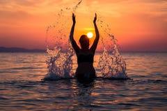 Silhueta da água de espirro fêmea com suas mãos no por do sol ov imagem de stock