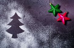 Silhueta da árvore de Natal na neve no fundo preto com as estrelas vermelhas e verdes Conceito do feriado Imagens de Stock