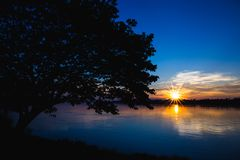 A silhueta da árvore na esquerda com rio e o sol alargam-se no por do sol fotos de stock royalty free