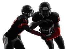 Silhueta da ação do jogo de passagem de dois jogadores de futebol americano Foto de Stock Royalty Free