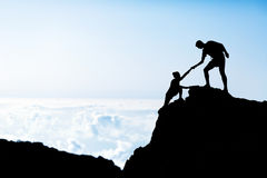 Silhueta da ajuda do homem e da mulher nas montanhas Fotos de Stock Royalty Free
