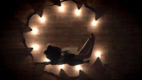 A silhueta da bailarina da moça está dançando na obscuridade, luzes ao redor, conceito do bailado, conceito do movimento, tiro su vídeos de arquivo