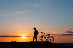 A silhueta da bicicleta nas montanhas Fotos de Stock