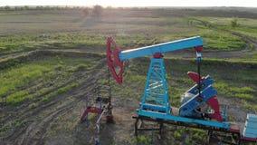 Silhueta da bomba de ?leo de trabalho do campo petrol?fero no por do sol O equipamento industrial filme