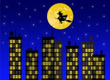 Silhueta da bruxa que voa sobre a cidade na noite imagem de stock