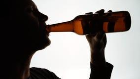 Silhueta da cabeça masculina que bebe de uma garrafa marrom filme