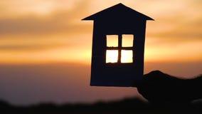 A silhueta da casa do papel no fundo do por do sol A mão de um homem guarda um modelo de uma casa de papel O conceito video estoque