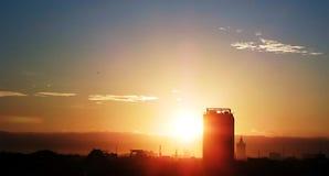 Silhueta da construção no nascer do sol atrás dos montes Foto de Stock Royalty Free