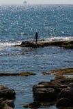 Silhueta da criança pequena que joga no recife perto do mar no por do sol Imagem de Stock