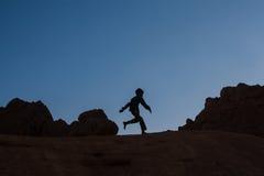 Silhueta da criança que corre sobre as rochas no deserto no por do sol Fotos de Stock Royalty Free