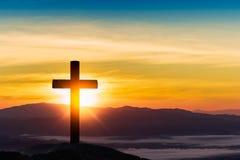 Silhueta da cruz no fundo do por do sol da montanha foto de stock royalty free