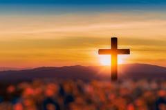 Silhueta da cruz no fundo do por do sol da montanha fotos de stock