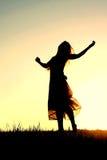 Silhueta da dança da mulher e do deus do elogio no por do sol imagem de stock royalty free
