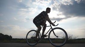 Silhueta da equitação do homem na bicicleta do vintage com o céu bonito do por do sol no fundo Ciclismo desportivo do indivíduo n vídeos de arquivo